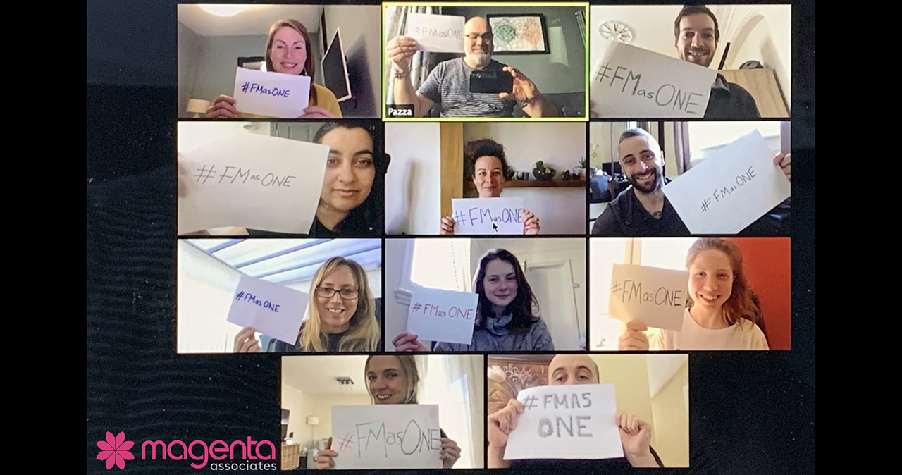 The Magenta Associates team hold up banners for the #FMasONE campaign this World FM Day