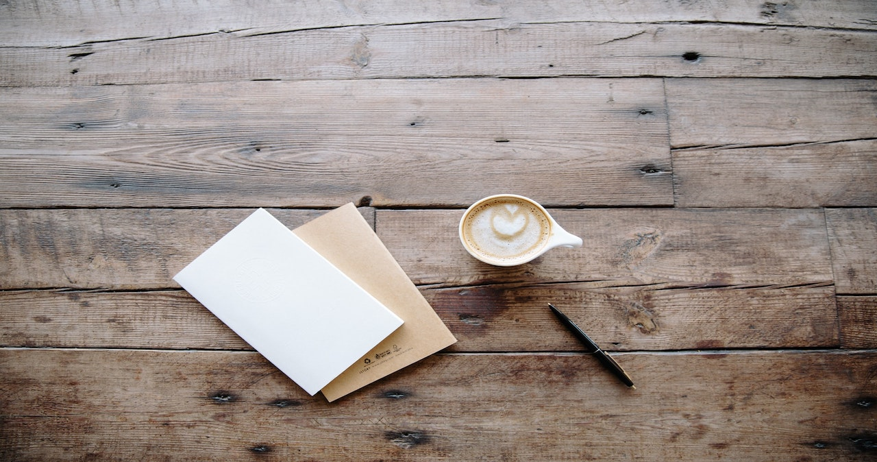 A letter and cup of coffee on a table