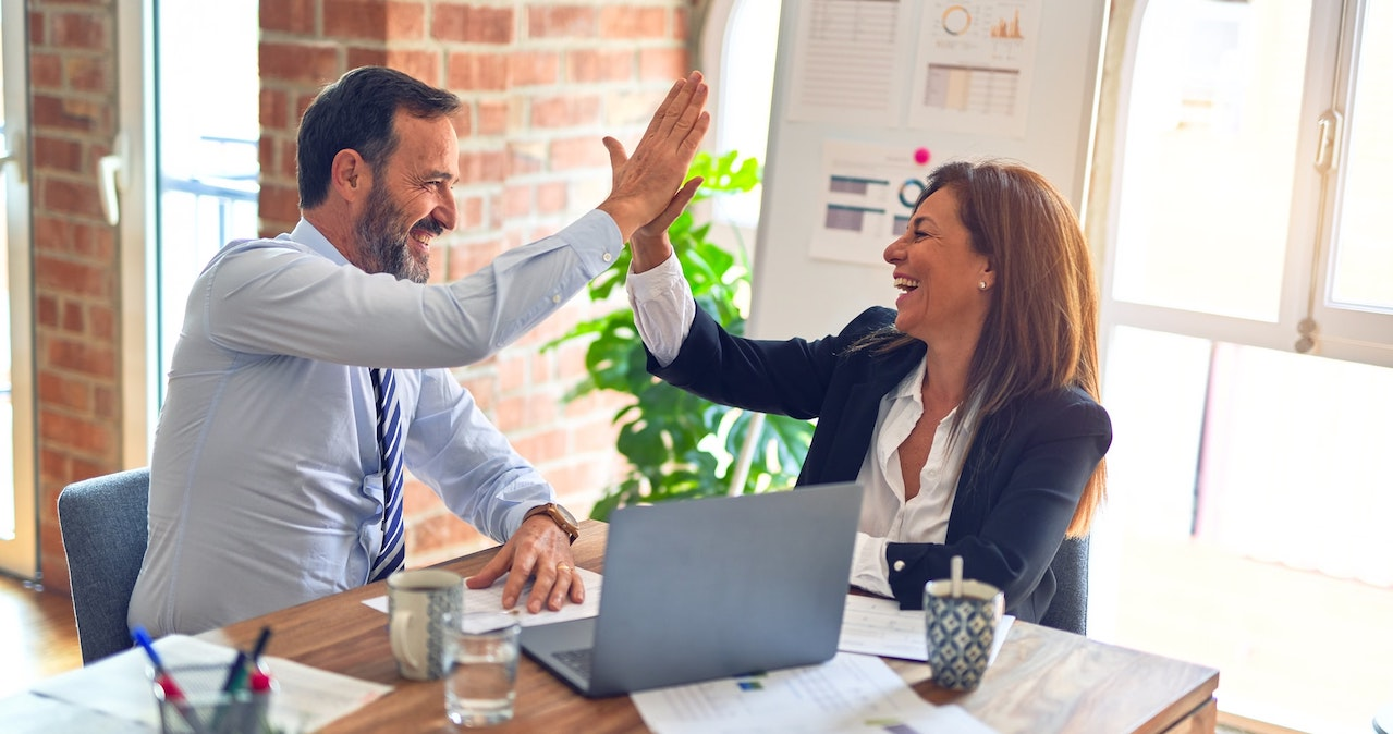 Two people high five in an office
