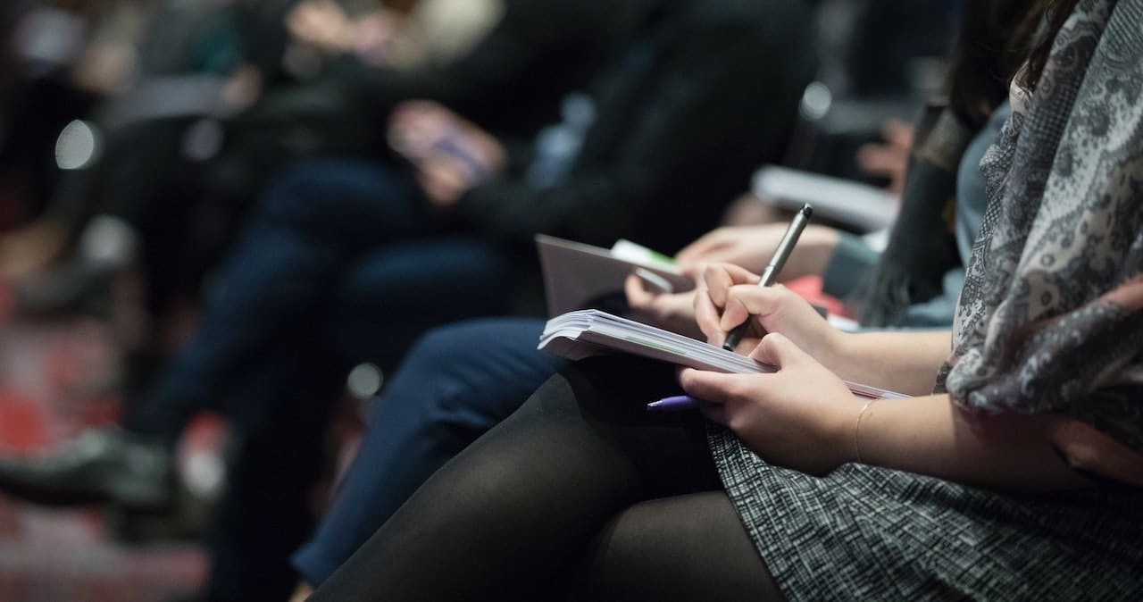 A journalist taking notes at a press conference