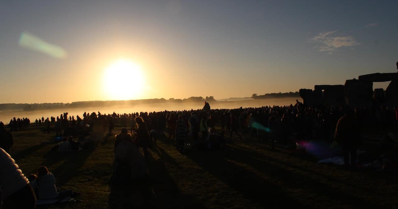 A sunset over a field of people