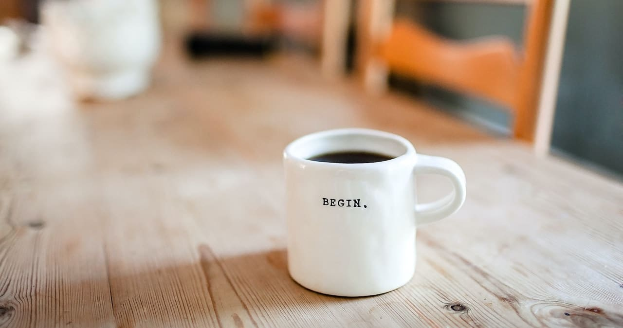 A coffee cup on a table with the word 'begin' on the side